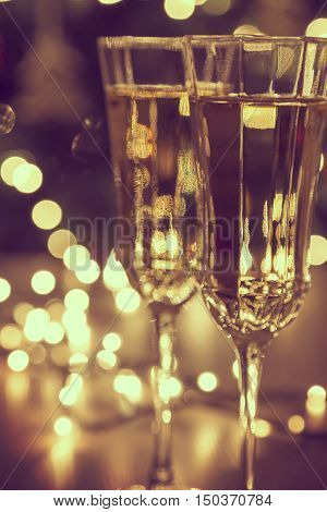 Close up of champagne glasses with the Christmas tree lights in the background. Selective focus