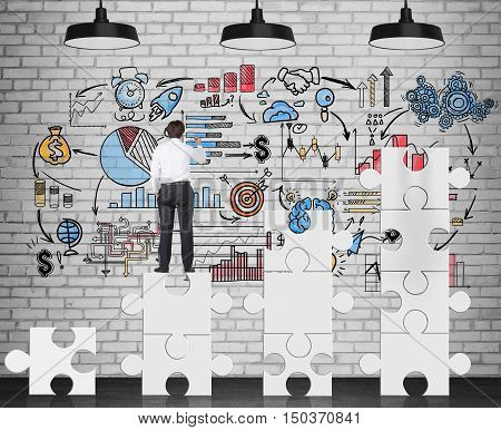 Rear view of businessman standing on white puzzle pieces and drawing business sketch on brick wall. Concept of management