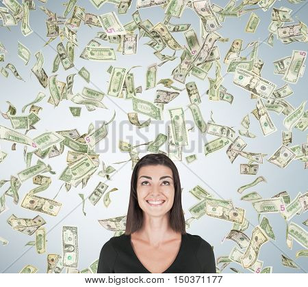 Smiling girl standing under dollar rain against light gray wall background. Concept of sudden money acquisition