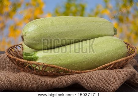 courgettes on the wooden table with sacking and a blurred background.