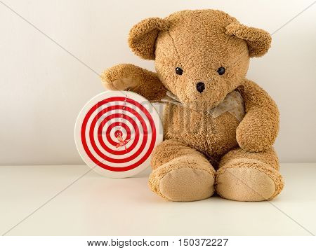 Brown teddy bear hold red dartboard with red bullseye dart arrow hit on center board. Concept of success target goal achievement.