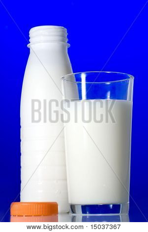 Milk in glass and open bottle isolated on blue