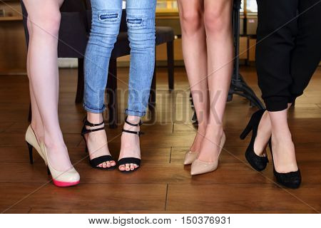 Slim legs in heels of four young women standing in cafe with wooden floor