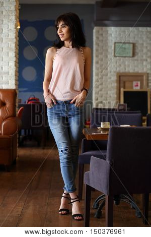 Young beautiful woman with black hair stands in cafe, shallow dof