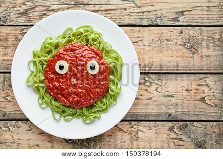 Spooky halloween monster green pasta with fake blood tomato sauce and mozzarella eyeballs on vintage wooden table background