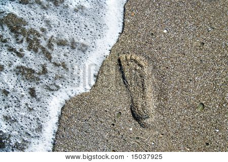 sand stones with footprint and water wave