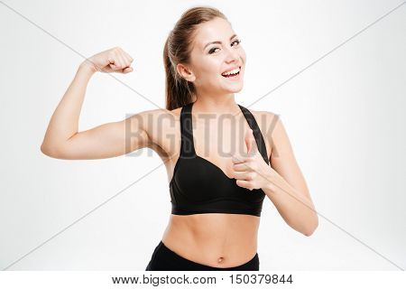 Happy sporty woman showing ok sign and biceps isolated on a white background