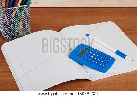 On The Exercise Book Into A Cell Lying Blue Calculator And Pen.