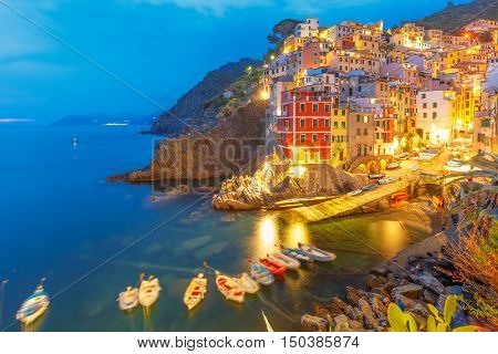Night aerial view of Riomaggiore fishing village, seascape in Five lands, Cinque Terre National Park, Liguria, Italy.