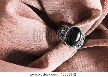 Vintage black onyx ring on crumpled beige silk as a background