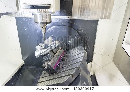 The 5-axis CNC machine while cutting the sample part of aircraft.The spindle of 5 axis CNC machining center while cutting turbine sample part of aircraft.