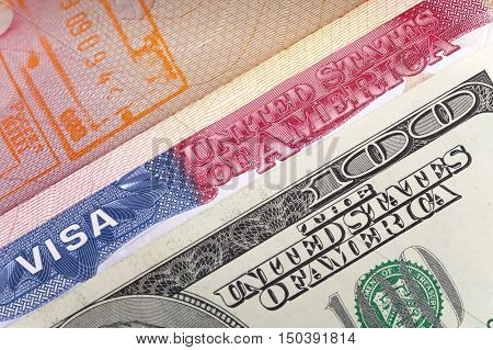 The American visa on page of the international passport and US dollars closeup