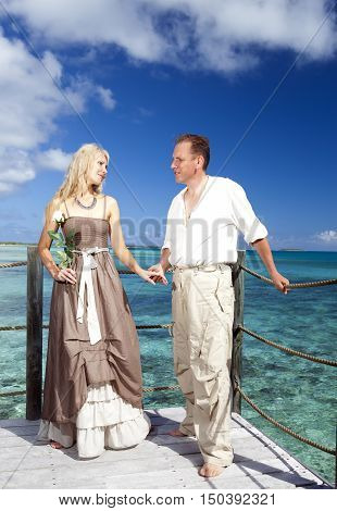 Loving couple on a wooden platform over the sea on the tropical island
