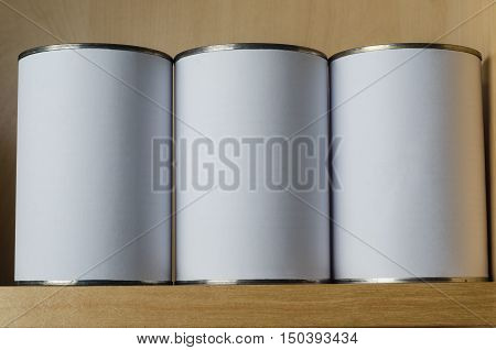 Three Tin Cans On Shelf With Blank White Labels