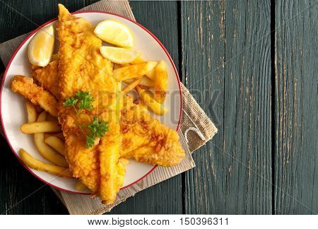 Close up of battered fish on a plate with chips