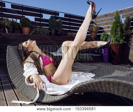 beauty young woman after spa in bikini and robe at hotel resort, on terrace enjoying warm sun, lifestyle people concept