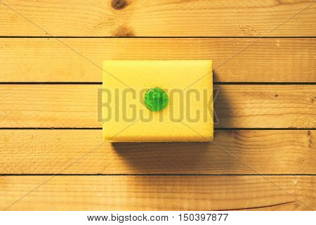 Yellow dish sponge with a drop of dishwashing detergent