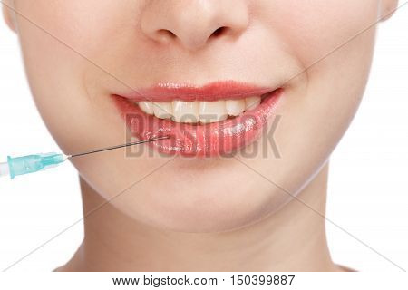Young beautiful smiling woman face with plastic surgery syringe injection on lips isolated on white background. Close up.