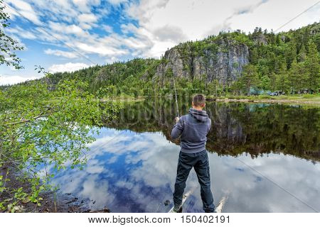 Young man fishing on a lake. view from the boat