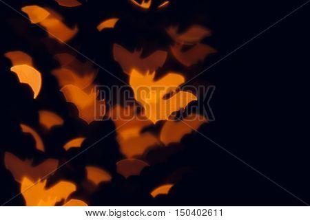 Halloween festive blurred background. Orange bats on a black background.