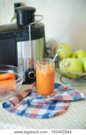 on the kitchen table is a fresh juice from carrots and apples standing next to a juicer and fruit