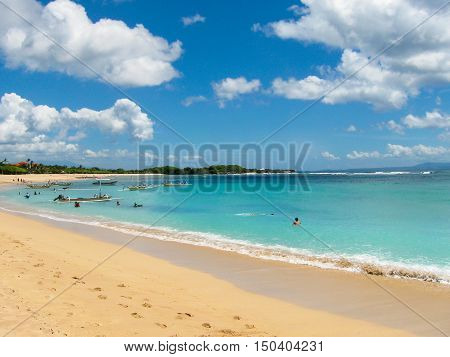 Beautiful white sand beach surrounded by tropical palm trees on the island of Bali in Nusa Dua area. Blue sky with white clouds, white sand and boats
