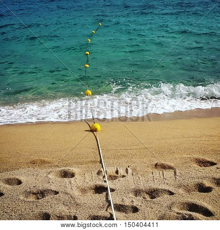 Rope with floats and footprints on the sea sand beach
