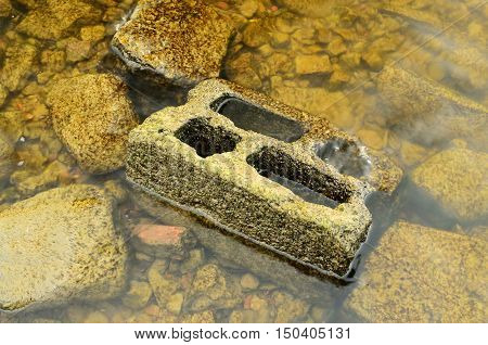 Stones covered with silt lie beneath the water.