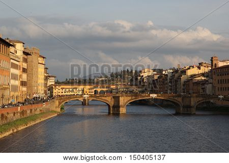 Panorama of the bridges over the River Arno, Florence, Italy - On the horizon you can see the hill, clouds floating in the sky, and the city's bustling even in the evening. Everything is full of life. If you listen, you can hear how machines beeping, stud