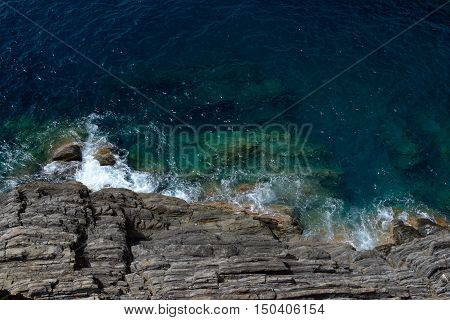 Rocky sea shore in Riomaggiore in Liguria Italy. One of five Cinque Terre cities (unesco world heritage)
