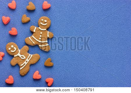 Gingerbread man and hearts holiday cookies on blue background top view blank space for recipe text