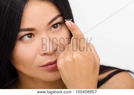 Closeup picture of pretty Korean or Asian woman looking at contact lens isolated on white background. Beauty, vision, eyesight, ophthalmology and people concepts.