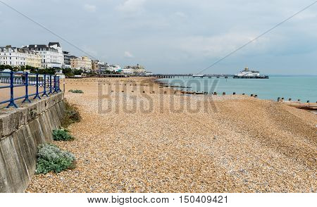 View along promenade and pebbly beach of Eastbourne towards the pier on cloudy day