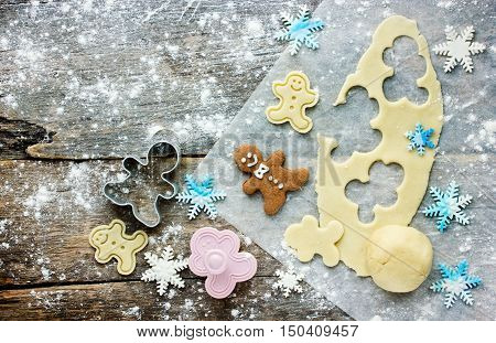 Christmas baking background: dough cookie cutters and snowflakes from sugar pastes on a wooden background. Viewed from above and space for text