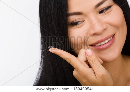 Closeup picture of happy smiling Korean or Asian woman looking at contact lens in front of her. Beauty, vision, eyesight, ophthalmology concepts.