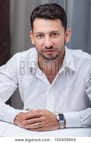 Middle Eastern Young attractive businessman with beard sitting at the table