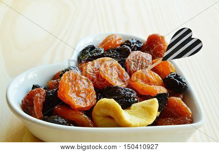 dried fruits in heart-shaped bowl and fruit toothpick with wooden table. dried fruits Apple,Pear,Prune,apricots.