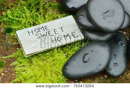 Home sweet home Text with stone and moss