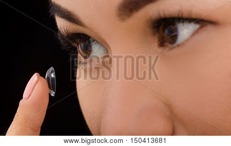 Beauty, vision, eyesight, ophthalmology and people concepts. Closeup of Korean woman putting on contact lenses.