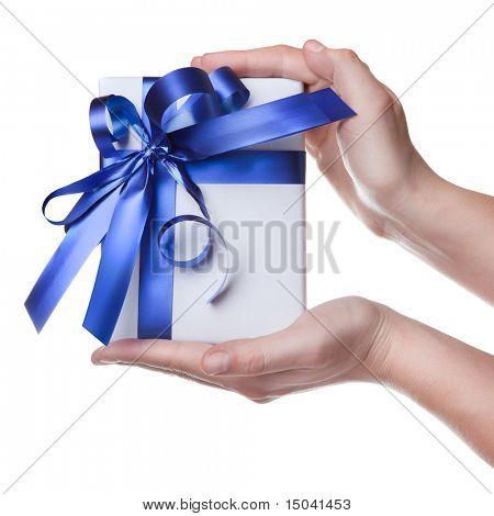 Manos sosteniendo el regalo en el paquete con cinta azul aislada en blanco