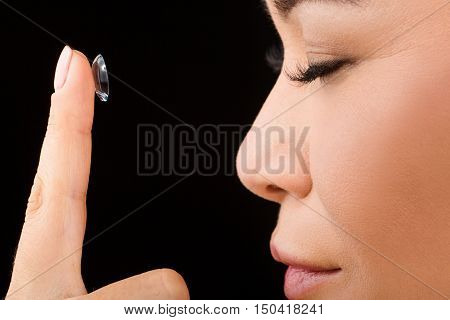 Closeup of woman posing with her eyes closed while putting contact lenses over black background in studio.