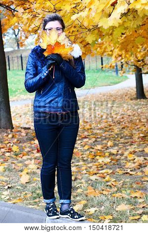 Woman walks in the autumn park, collecting leaves. Woman looks in a lens. Vertical full-length portrait