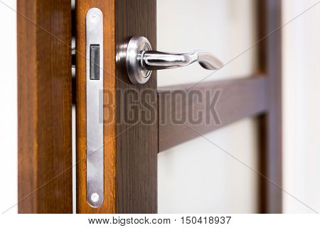 Part of wooden open door with silver door-handle