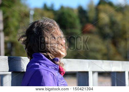 Woman daydreaming. Wind blowing her hair. Forest on background.