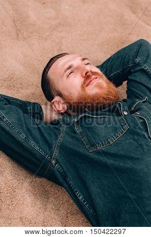 Pensive dreams hipster bearded man lying on the sand beach