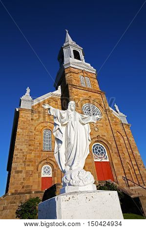 Statue in front of The church of Saint-Pierre in the Acadian village of Cheticamp, Cape Breton, Nova Scotia, Canada