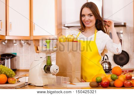 Woman young housewife in kitchen with fruits and juicer preparing to make fresh juice. Healthy eating cooking vegetarian food dieting and people concept.