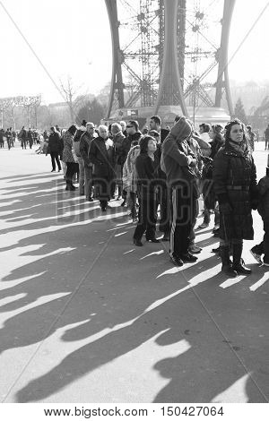 PARIS, FRANCE - March 3, 2011: Tourists and their shadows in a queue to The Eiffel Tower in Paris.  Black and white image