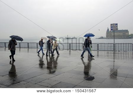 Istanbul, Turkey - April 18, 2014: Istanbul Kadikoy Steamboat pier. People walking in the rain pier. Strait of Istanbul Kadikoy Pier ferries are the most popular form of public transport in Istanbul for.
