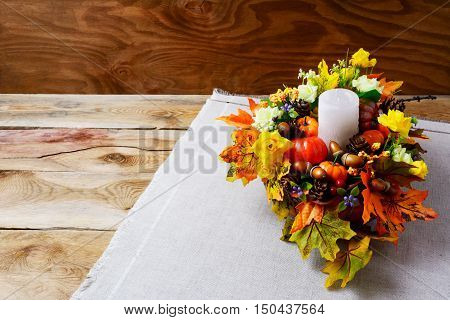 Thanksgiving centerpiece with candle and artificial fall leaves. Thanksgiving background with fall decor. Fall background. Copy space.